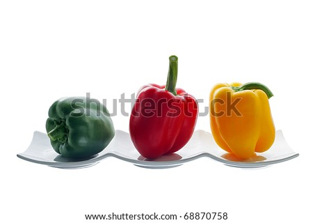 one red, one yellow and one green pepper on white dish
