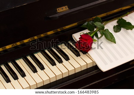 one red rose with notes paper on vintage piano - stock photo