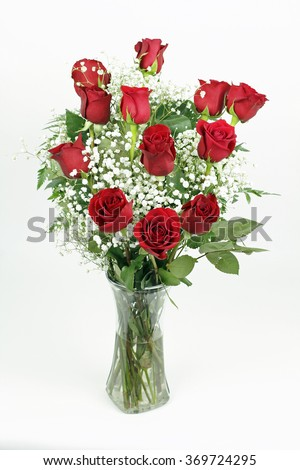 One red roses flower arrangement with its leaves and white babies breath blossoms in a clear glass vase. A dozen fresh cut red roses with babys breath in a glass vase - stock photo