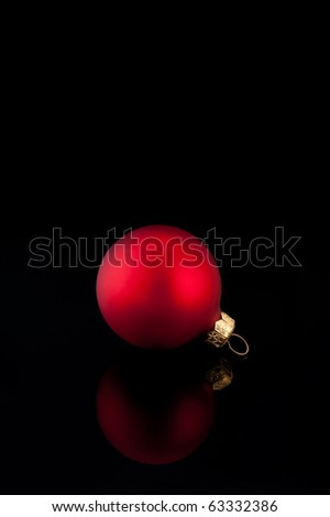 One red satin Christmas ball on black background with reflection - stock photo