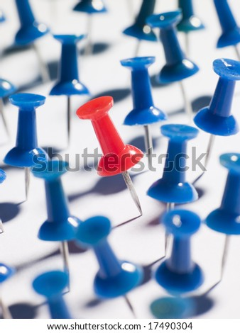 One Red Thumbtack Amid Blue Thumbtacks - stock photo