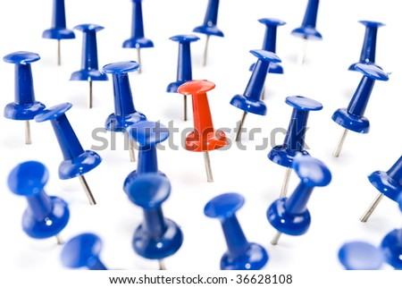 One red thumbtack amid blue thumbtacks. Selective focus - stock photo
