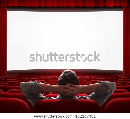 one relaxed man sitting alone with comfort like at home in front of big screen in empty cinema hall - stock photo