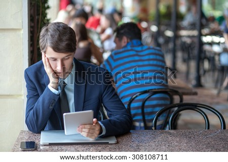 One relaxed young handsome professional businessman working with his laptop, phone and tablet in a noisy cafe. holding tablet and reading.   - stock photo