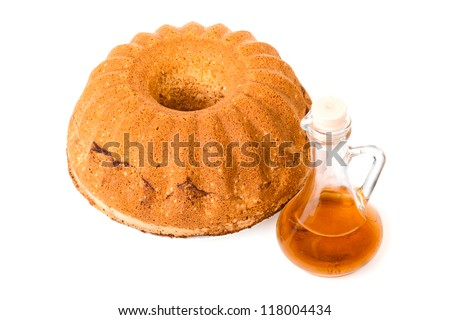 One round cake with a decanter isolated on white background