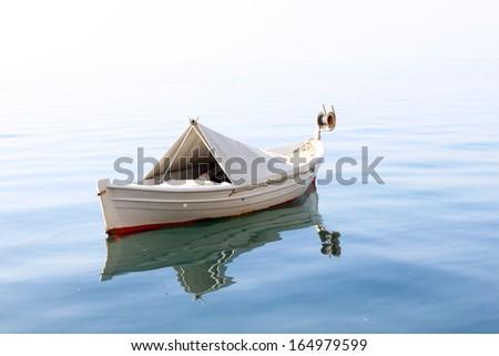 One rowing boat in the open sea. Photo taken in Thessaloniki, Greece. - stock photo