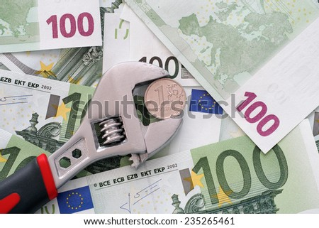One ruble coin grip in a adjustable wrench on euro banknotes. - stock photo