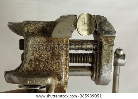 One russian rouble under pressure in old rusty vise. Russian economic crisis concept. - stock photo