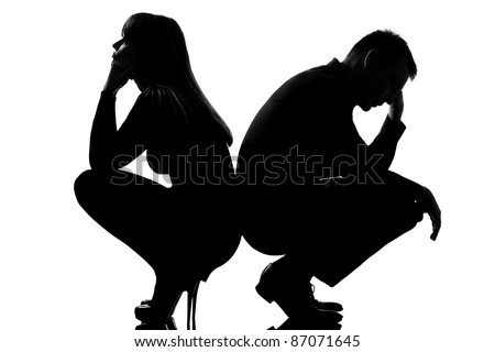 one sad caucasian couple man and woman crouching back to back in studio silhouette isolated on white background - stock photo