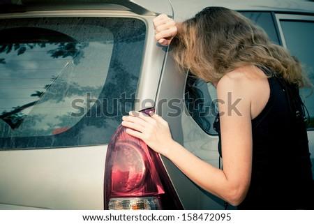one sad woman  near a car - stock photo