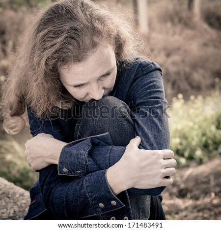 one sad woman sitting  near a river - stock photo