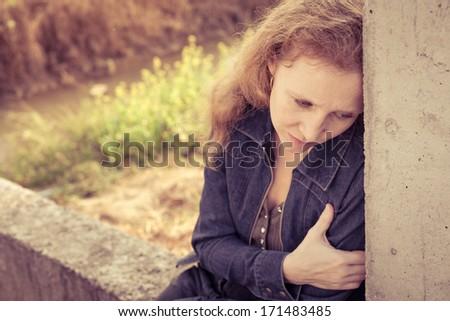 one sad woman sitting  near a  wall - stock photo