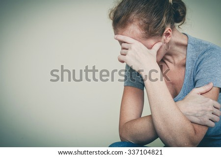 one sad woman sitting near a wall and holding her head in her hands - stock photo