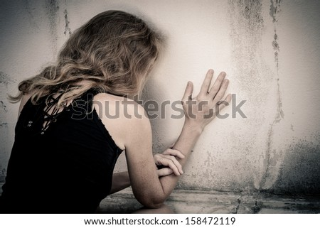 one sad woman sitting on the floor near a wall  - stock photo
