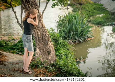 one sad woman standing  near a river - stock photo