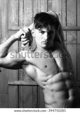 One seductive beautiful sexy cool stylish young hunk man with dark short hair looking straight topless with strong biceps and abdominal muscles standing on wooden background studio closeup, vertical  - stock photo