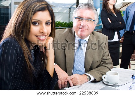 one senior business man and a young business woman meeting in coffee shop - stock photo