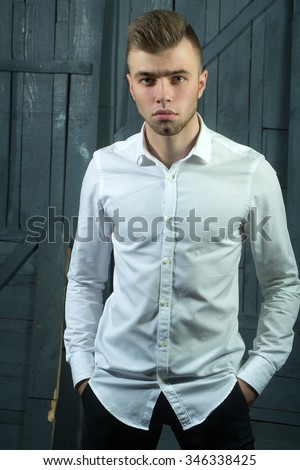 One sensual young handsome man with beautiful hairstyle in white shirt with bow standing in studio on wooden background, vertical picture - stock photo