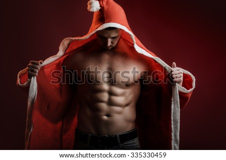One sexual strong young new year man with muscular body in red and white christmas santa coat standing posing on studio background, horizontal picture - stock photo