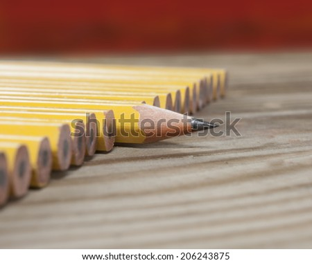 One sharp pencil in a line of  pencils - stock photo