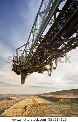 One side of huge mining drill machine photographed from a ground with wide angle lens. Dramatic and colorful sky in background. - stock photo