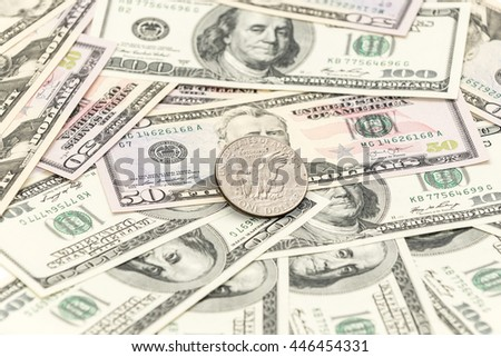 One silver dollar with hundreds and fifty banknotes as background