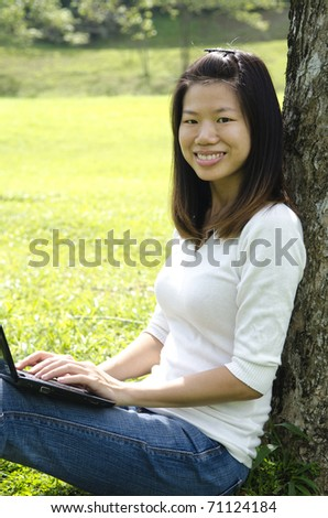 one single asian girl using laptop outdoor - stock photo