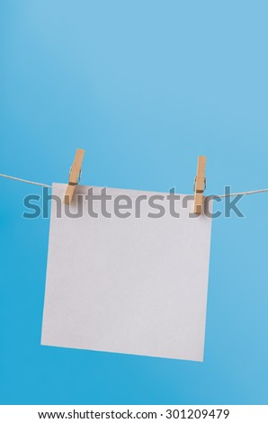 One, single sheet of white, square paper, hanging from a clothes line on wooden pegs against a clear blue sky.  Left blank for copy space. - stock photo