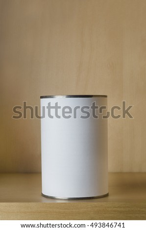 One single tin can (aluminum) with blank white label on shelf with copy space above.