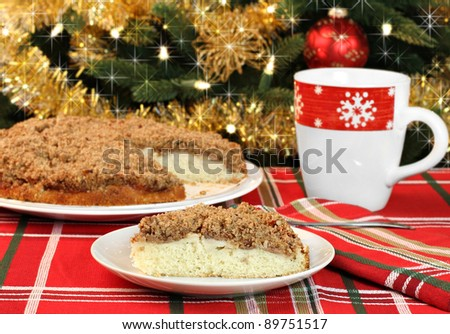 One slice of apple streusel cake in front of a sparkling Christmas tree.  Whole cake in background. - stock photo