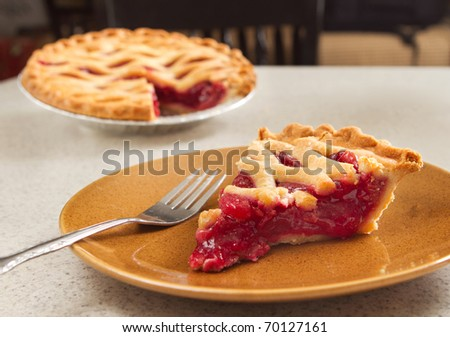 one slice of cherry pie ready to eat with a fork taken from the whole - stock photo