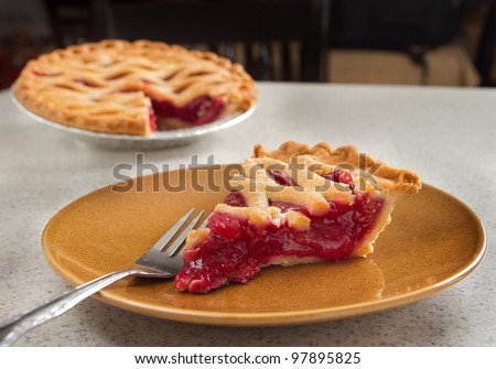 one slice of cherry pie removed from the whole and ready to eat - stock photo