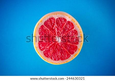 One slice of grapefruit on a blue background, horizontal shot - stock photo