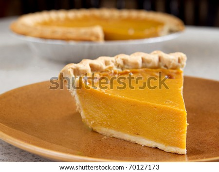 one slice of pumpkin pie cut from the whole - stock photo