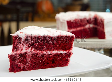 one slice of red velvet cake in front of the whole dessert - stock photo