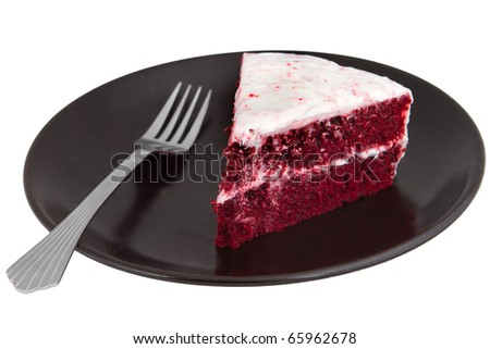 one slice of red velvet cake on a black plate with a fork isolated over white - stock photo