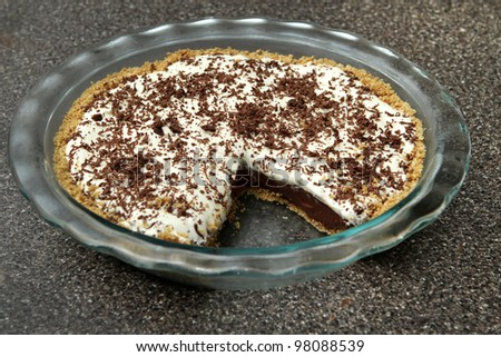 one slice removed from a chocolate cream pie in a glass plate - stock photo