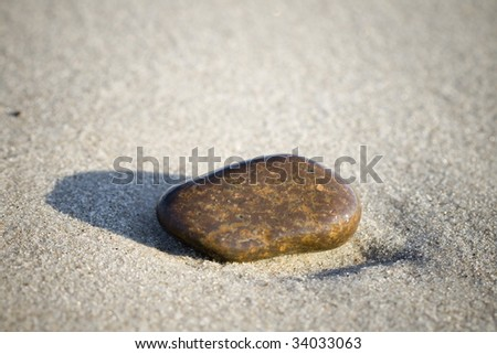 [Image: stock-photo-one-small-brown-stone-in-sand-34033063.jpg]