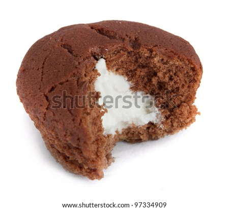 one small cupcake with a bite removed showing filling - stock photo