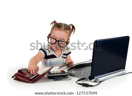 One small little girl wearing t-shirt with stripes, calling phone, credit cards, calculator, notebook are on the table. Business concept. Isolated object.