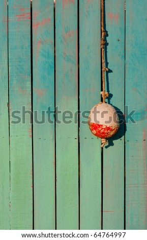 One small white and red fishing buoy hangs on hook in front of brightly painted wooden shack - stock photo