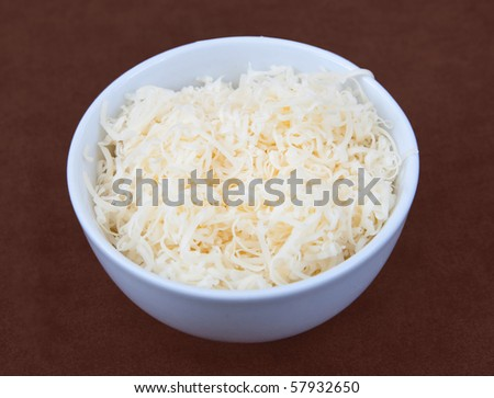 one small white prep bowl full of shredded cheese ready to cook. - stock photo
