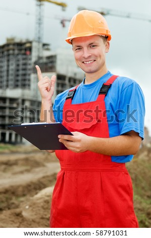 One smiley builder worker with clipboard and finger pointing up at construction site - stock photo