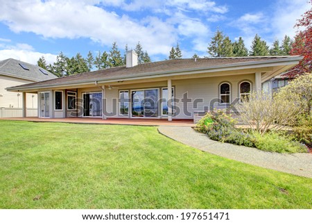 One story house with backyard column porch, lawn and walkway