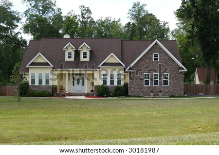 One story residential home with both brick and board siding on the facade. - stock photo