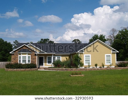 One story residential home with vinyl siding and brick or stone on the facade. - stock photo
