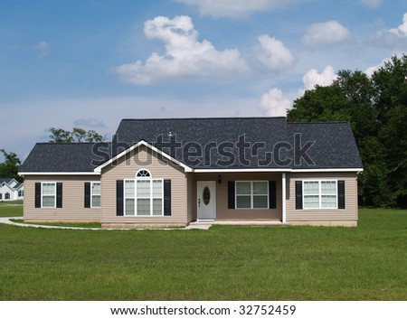One story residential low income home with vinyl siding on the facade. - stock photo