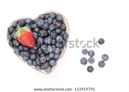 One strawberry and bluberries in a heart shaped bowl against a white background