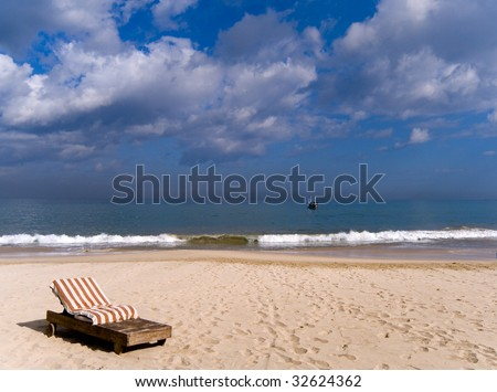 One striped chaise lounge on an ocean coast - stock photo