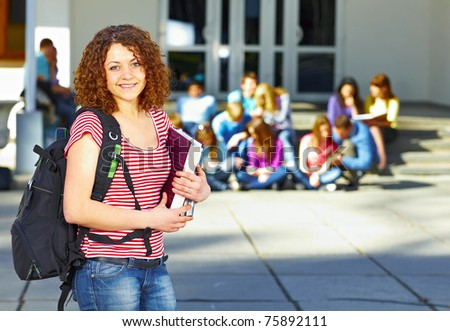 One student with book in front of group of students near the university